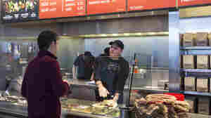 A Chipotle Mexican Grill employee prepares a burrito for a customer in Seattle. The CDC believes the two recent E. coli outbreaks at Chipotle restaurants are over.