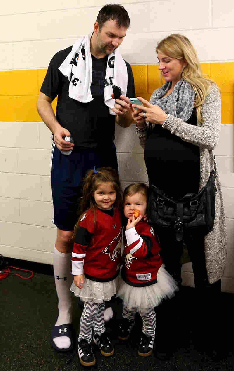 John Scott talks with his wife, Danielle, after the 2016 NHL All-Star Game, as their kids amuse themselves.