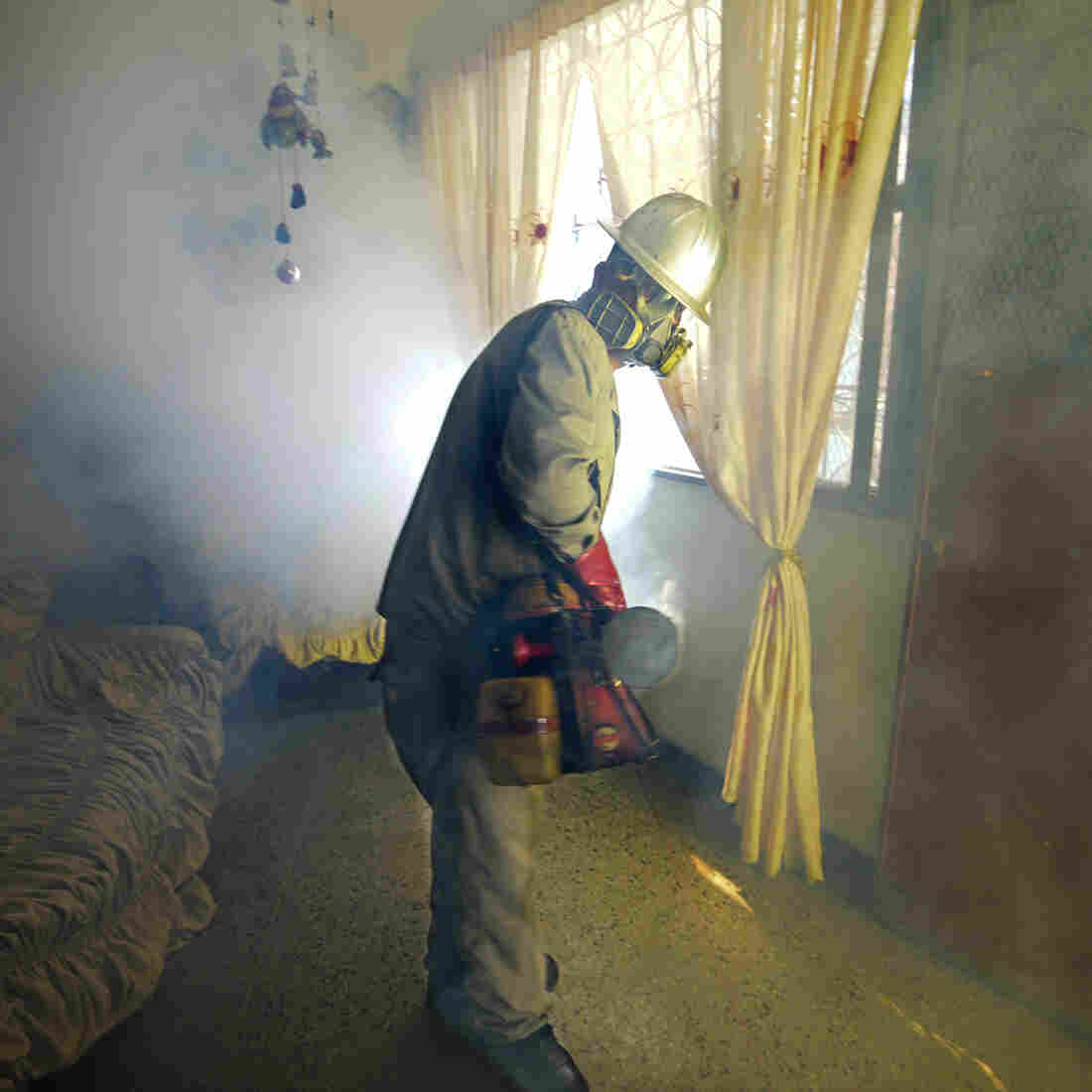 A Health Ministry employee fumigates against the Aedes aegypti mosquito, which can carry the Zika virus, at a home in Caracas, Venezuela, on Jan. 28.