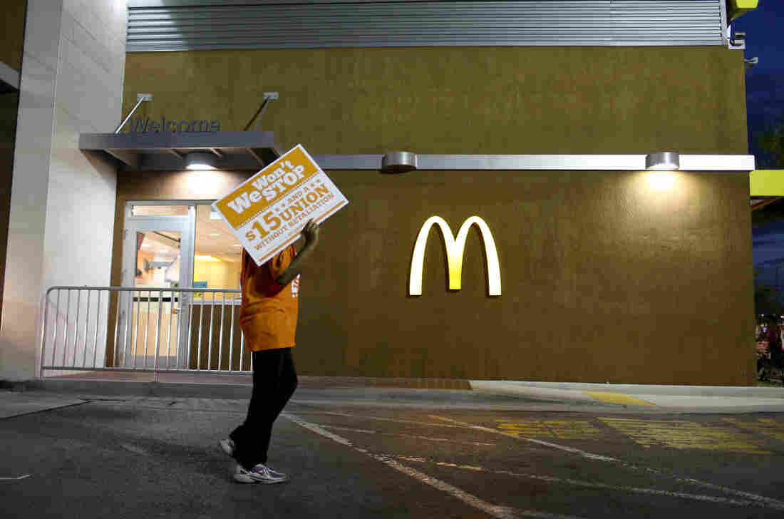 """Protesters gather at a McDonald's to ask for higher wages on April 15, 2015 in Miami Gardens, Fla. Food labor advocate Saru Jayaraman writes in a new book that the company has taken the """"low road"""" and lobbied extensively for lower wages and working conditions standards at the federal and state levels."""