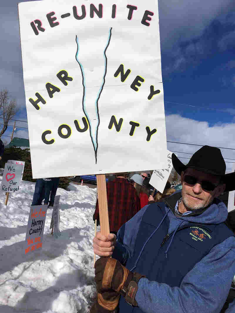 Burns resident Leon Pielstick carries a sign outside the Harney County Courthouse on Monday.