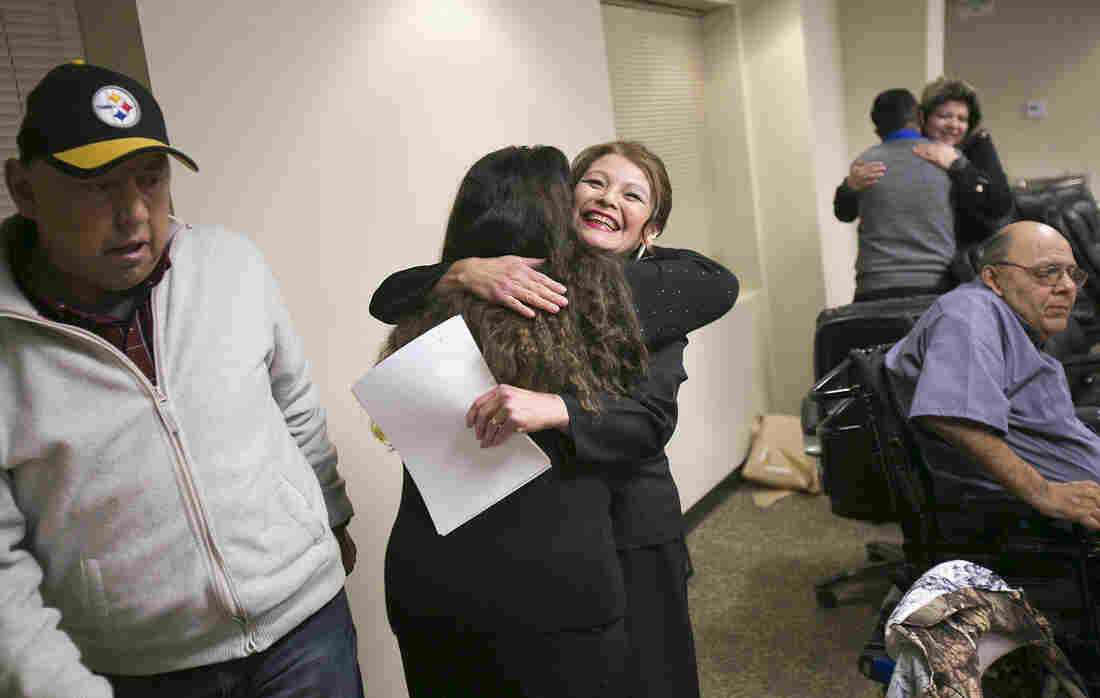 """Wilder, Idaho, Mayor Alicia Mora Almazan (center) receives a congratulatory hug after a swearing-in ceremony at City Hall. At left is City Council member Robert Rivera, and at right is City Council member Guadalupe """"Lupe"""" Garcia."""