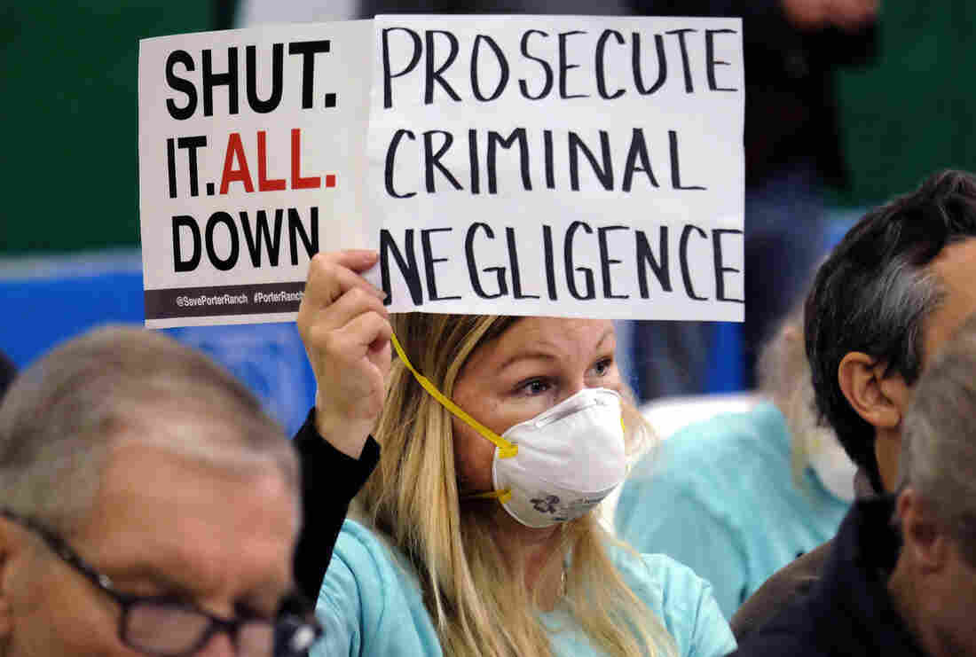 On Jan. 16, Tera Lecuona, resident of the Porter Ranch area of Los Angeles, holds a protest sign during a hearing over a gas leak at Southern California Gas Co.'s Aliso Canyon Storage Facility. The company faces misdemeanor charges as well as numerous civil lawsuits.