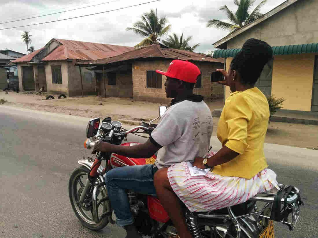 Beata Felix Rutabingwa, a World Bank consultant, captures street photos on a motorcycle in Dar es Salaam, Tanzania.