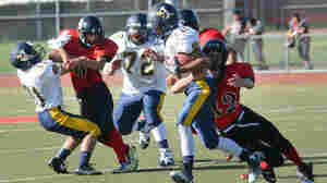 Garrison Pennington (right, No. 42) tackles a player during Albany High School's 2014-2015 season — the last he would play.