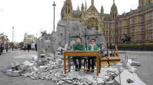 Two children whose school was bombed in Aleppo pose in a mock destroyed classroom — set up by the charity Save the Children — outside the Houses of Parliament in London on Wednesday, one day before a donor conference aiming to raise money for victims of Syria's war.