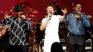 Maurice White flanked by singers Ralph Johnson (left) and Philip Bailey (right) of the band Earth, Wind & Fire perform at the Wiltern Theater December 11, 2004 in Los Angeles.