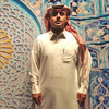 "Saudi artist Abdulnasser Gharem poses in front of ""Generation Kill,"" a piece made with rubber stamps, digital print and paint, at the opening night of his exhibition titled Al Sahwa (The Awakening) at Ayyam gallery in Dubai in 2014."