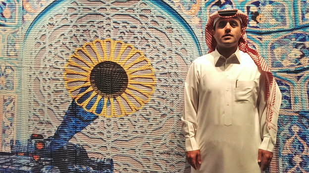 """Saudi artist Abdulnasser Gharem poses in front of """"Generation Kill,"""" a piece made with rubber stamps, digital print and paint, at the opening night of his exhibition titled Al Sahwa (The Awakening) at Ayyam gallery in Dubai in 2014. (AP)"""