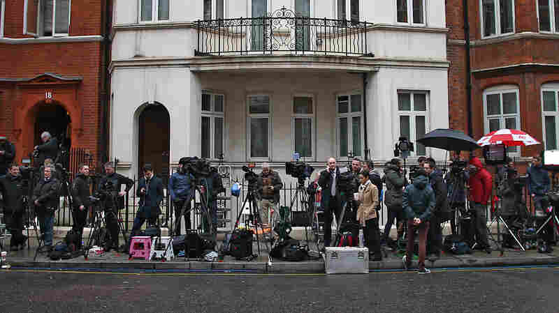 Journalists work outside the Ecuadorian Embassy where WikiLeaks founder Julian Assange has been holed up since 2012. A U.N. panel says he deserves compensation for being arbitrarily detained.