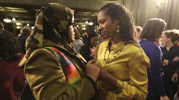 Former Wheaton College professor Larycia Hawkins (right) is greeted by supporter Donna Demir after a news conference on Jan. 6 in Chicago. Hawkins, who's Christian, was suspended by Wheaton, an evangelical Christian school, after she said Muslims and Christians worship the same God. Administrators initiated steps to fire her. On Saturday the professor and school announced they'd parted ways. (AP)
