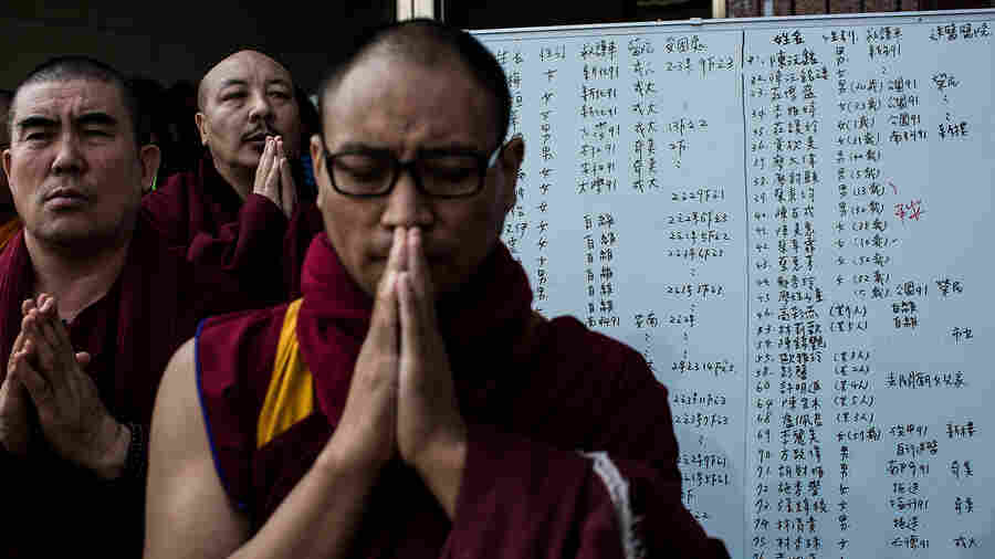 Monks pray near a list of the patients near a collapsed building on Sunday in Tainan, Taiwan.