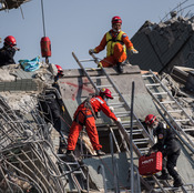 Rescue workers look through the rubble of a collapsed building in the southern Taiwanese city of Tainan on Sunday, following a strong 6.4-magnitude earthquake that struck early on Saturday. For more than 30 hours, rescuers have worked to free more than 120 people buried under the rubble of the apartment complex.