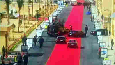 Egyptian President Abdel-Fattah al-Sisi's motorcade drives on a red carpet during a trip to open a social housing project in a suburb of Cairo on Saturday. One local newspaper devoted its entire front page Monday to accusing Sisi of decadence even as he asks Egyptians to tighten their belts.