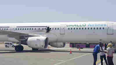 A hole is seen in a plane operated by Daallo Airlines as it sits on a runway at the airport in Mogadishu, Somalia, on Tuesday.