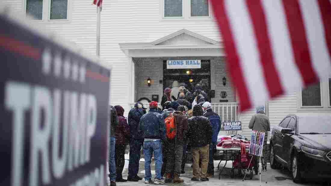 People wait in line amid falling snow to enter a Monday campaign event for Republican presidential candidate Donald Trump at the Lions Club in Londonderry, N.H.