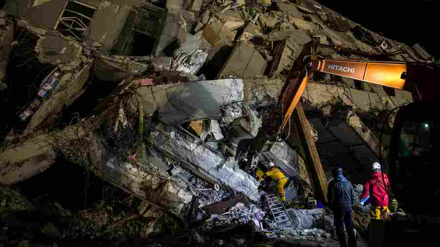 Rescue workers look for survivors in the remains of a building that collapsed in the 6.4 magnitude earthquake, in the southern Taiwanese city of Tainan.