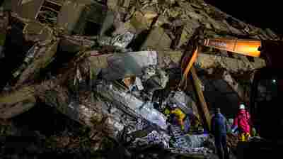 Rescue workers look for survivors in the remains of a building which collapsed in the 6.4 magnitude earthquake, in the southern Taiwanese city of Tainan.