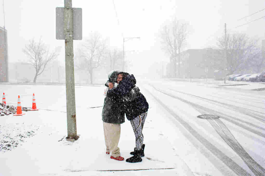 Jeneyah McDonald hugs Tyrone Knight, a previously homeless veteran, after spotting him walking along the road while out on a water run. McDonald met Knight while working to find him housing during her time working at My Brother's Keeper, a homeless shelter in Flint.
