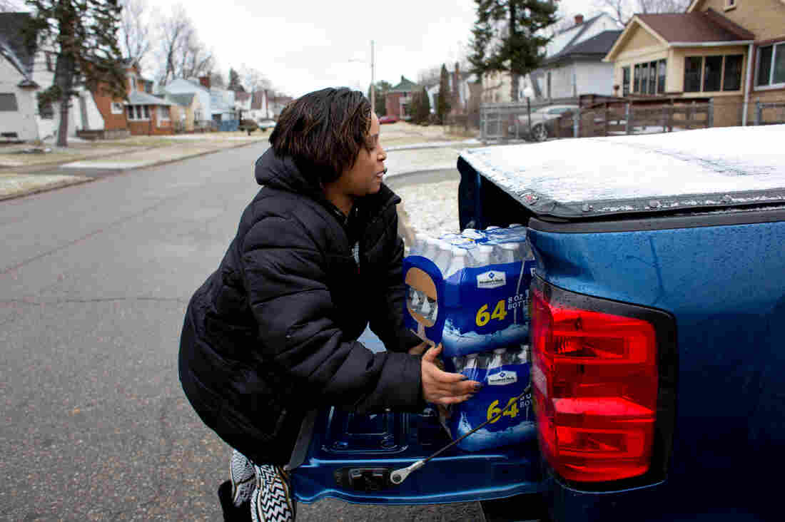 McDonald unloads cases of bottled water from her car to bring to her godbrother Brent Diggs, who is handicapped and often unable to pick up water himself, at his home in Flint.