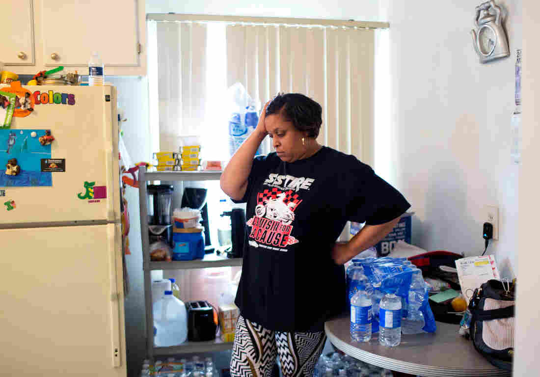 Jeneyah McDonald stands amid cases of bottled water in the kitchen of her home in Flint, Mich. Before water donations arrived in Flint, McDonald estimates she spent $100 out of her $300 weekly grocery bill buying safe water for her family.