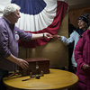 A resident hands election official Les Schoof a Republican ballot at the town hall polling site during the New Hampshire presidential primary election in Hart's Location, N.H., on Tuesday.