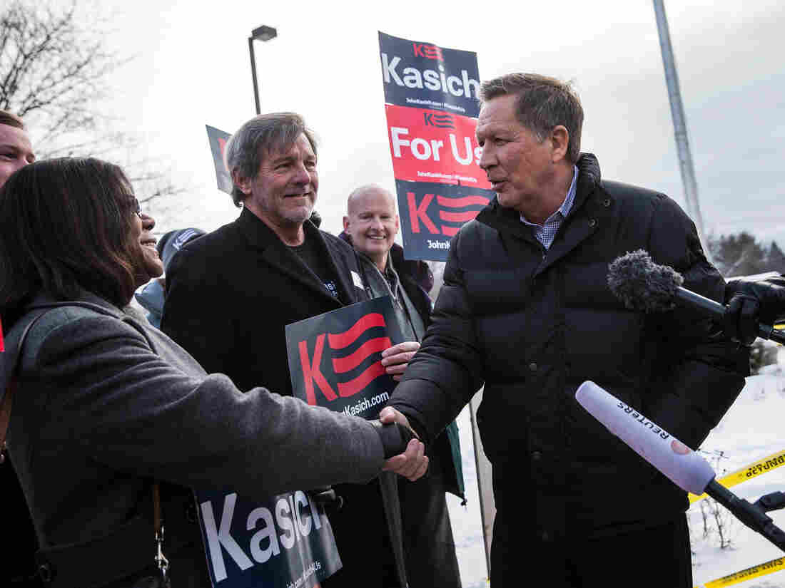 Republican presidential candidate John Kasich shakes hands with supporters outside Manchester High School, a voting location for the New Hampshire state primary.