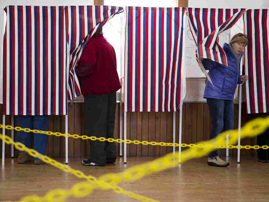 A woman emerges from the voting both in Chichester, N.H., on Tuesday.