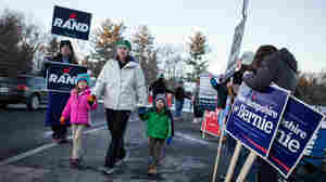 Voters pass by people campaigning for candidates as they make their way to the polls at Broad Street Elementary School on primary day in Nashua.