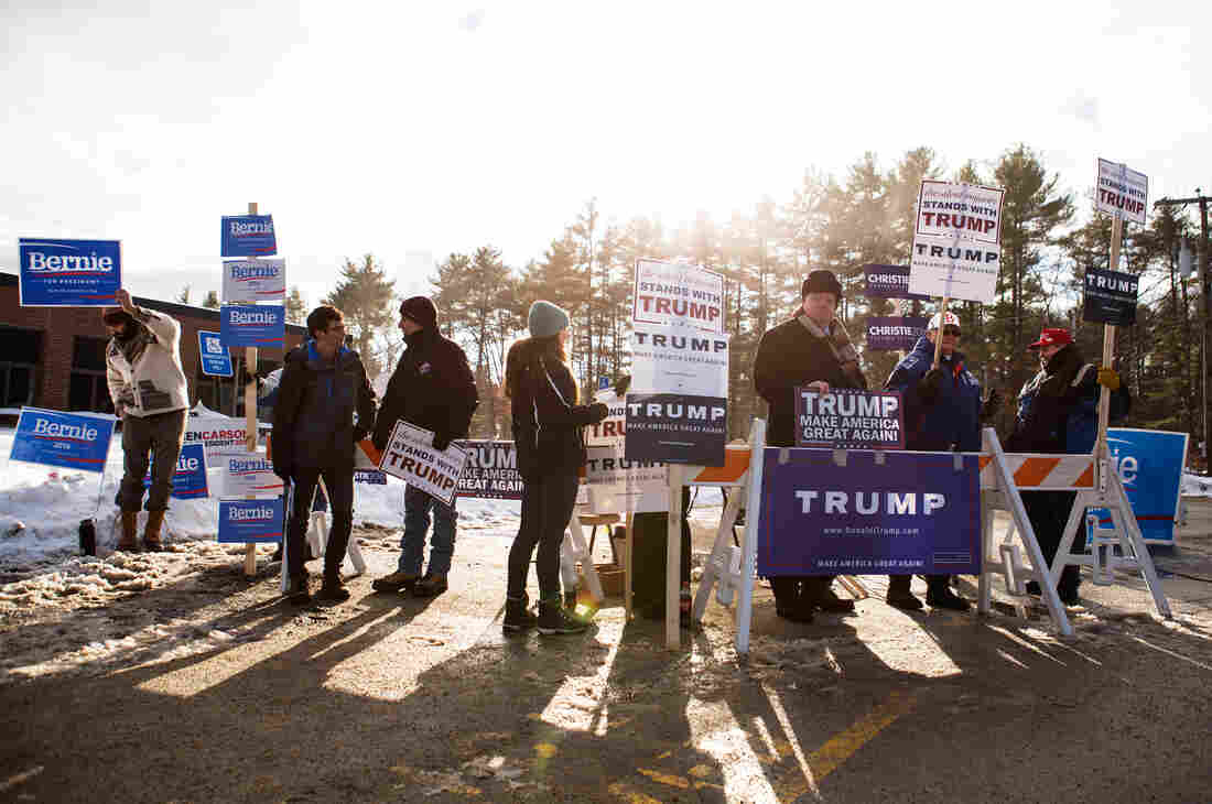 Supporters rally for their candidates outside of the voting place at Merrimack High School in Merrimack, N.H., for Tuesday's primary.