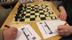 Chess players score a game at the facility.