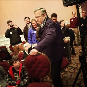 Bush helps put out additional chairs at his final New Hampshire town hall in Portsmouth Monday evening.