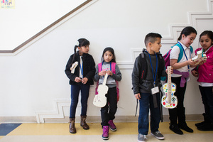 Students line up with their cardboard violins before going to their next class.