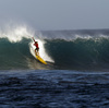 A surfer catches a wave at Waimea Bay after the In Memory of Eddie Aikau surfing contest was canceled on Wednesday.