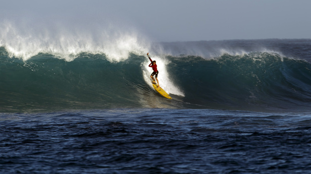 A surfer catches a wave at Waimea Bay after the In Memory of Eddie Aikau surfing contest was canceled on Wednesday. (AP)
