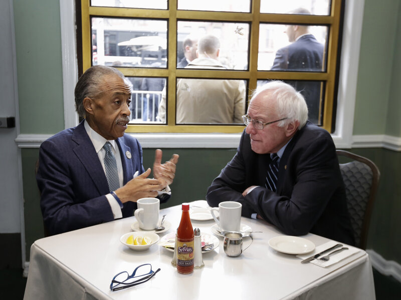 The Rev. Al Sharpton talks with Sen. Bernie Sanders at Sylvia's Restaurant in Harlem the morning after Sanders' New Hampshire primary victory over Hillary Clinton.