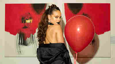 Rihanna in October 2015, in front of the cover art for her album, Anti.