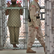 A detainee holds onto a fence as a U.S. military guard walks past.