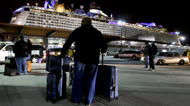 A passenger from the Royal Caribbean cruise ship Anthem of the Seas waits for transportation after arriving at the Cape Liberty cruise port in Bayonne, N.J., Wednesday. The ship was forced to turn around after hitting a strong storm at sea. (AP)