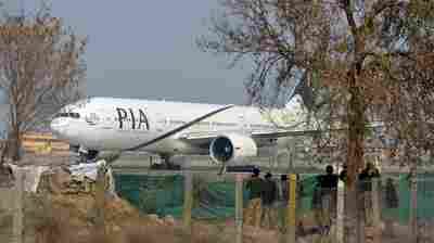 Pakistan policemen stand guard as a Pakistan International Airline plane taxis on a runway in Islamabad on Feb. 8. The national carrier has struggled in recent years with a $3 billion debt.