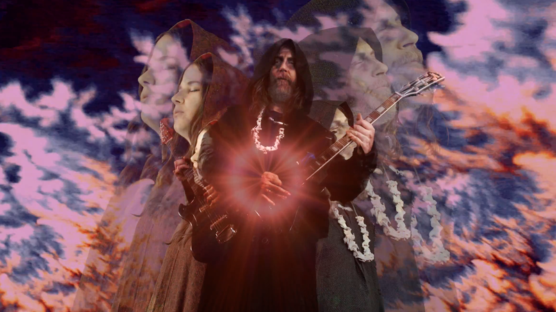 "Hooded figures perform against a surreal landscape in a scene from Black Mountain's new video for the song ""Mothers Of The Sun."""