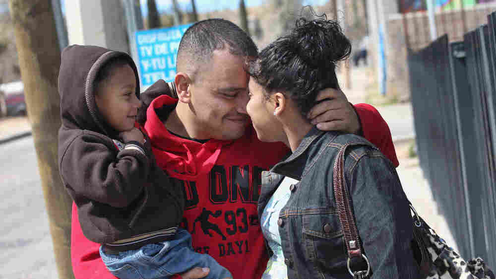 American citizen Lace Rodriguez and her husband Javier Guerrero from Mexico, embrace with their son Javier Jr., on March 10, 2013 in Nogales, Mexico.