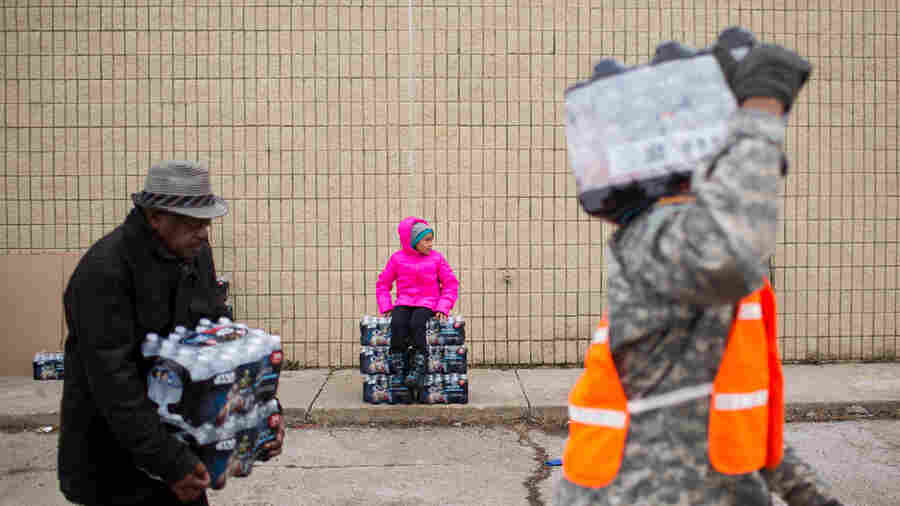 Zariah Garner, age 9 of Flint, rests on a stack of water as National Guard members and civilians carry cases to vehicles.