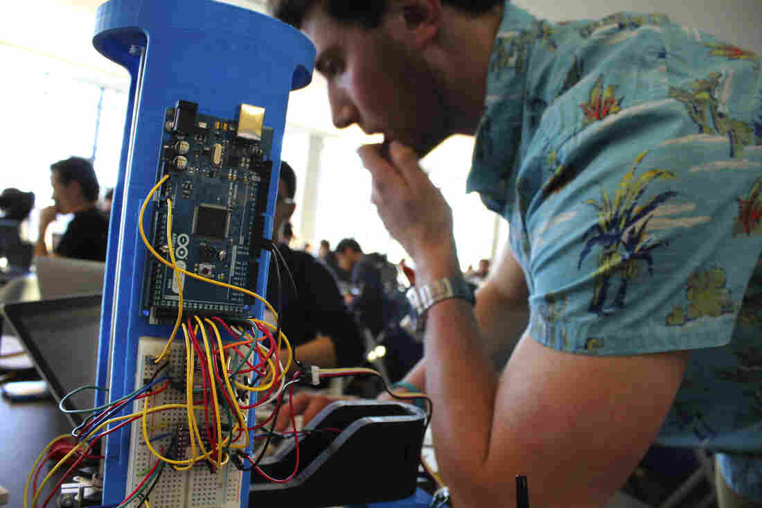 David Kaplan, a University of Maryland, College Park sophomore, tinkers with a robotic arm programmed to play tic-tac-toe at the Georgetown Hackathon in Washington, D.C.