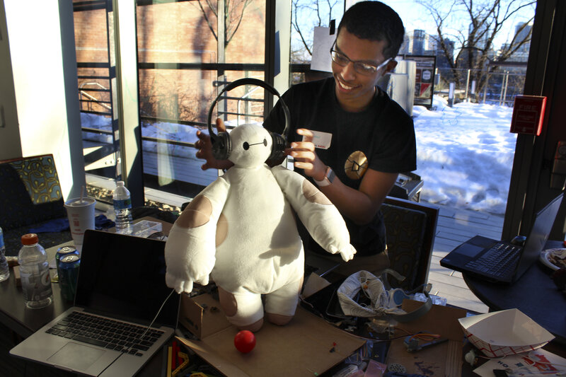"Ammar Al-Kahfah plays with a stuffed ""Baymax"" toy at the Georgetown Hackathon in Washington, D.C. His team has wired it to move and to collect basic medical information."