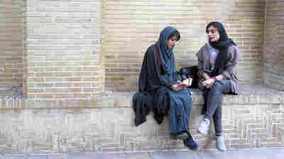 Shaghayagheh Aghazadeh and Atikeh Karimi sit at the tomb of the 14th century Persian poet Hafez in Shiraz, Iran.