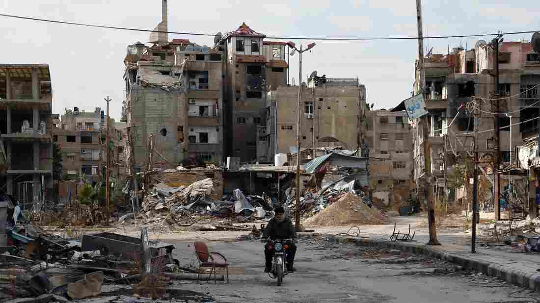 A man drives his motorbike past damaged buildings on Wednesday in the city of Harasta, east of the Syrian capital, Damascus.