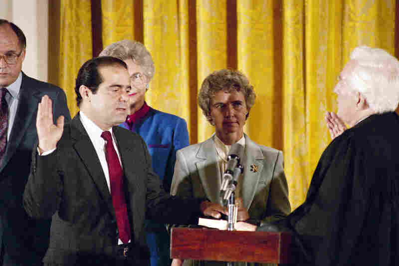 In this Sept. 26, 1986, file photo, retiring Chief Justice Warren Burger (right) administers an oath to Associate Justice Antonin Scalia, as Scalia's wife, Maureen, holds the bible during ceremonies in the East Room of White House.