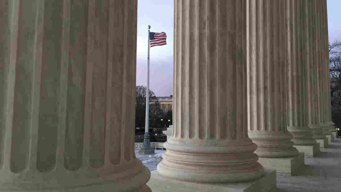 The American flag, seen through the columns of the Supreme Court building, blows in the wind on Feb. 13.