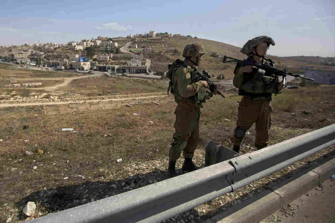 Israeli soldiers stand guard on the main road during the funeral of Dalia Lemkus on Nov. 11, 2014. Lemkus, who lived in the West Bank Jewish settlement of Tekoa, was killed in a stabbing attack.